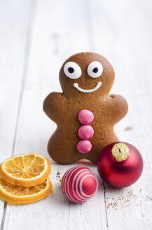 Smiling gingerbread man, orange slices and two christmas baubles on white wood - ODF000861