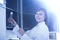 Portrait of smiling young female natural scientist working at microbiology laboratory - SGF001020