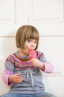 Portrait of little girl eating raspberry ice lolly - LVF002292