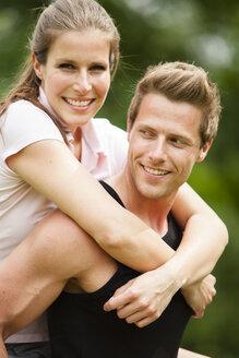 Man carrying smiling young woman piggyback - CvKF000161