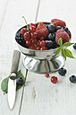 Metal bowl of different berries and a knife on white wood - ASF005494