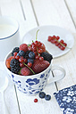 Cup of different berries on white wood - ASF005489