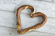 Heart shaped pretzel on white wood - ASF005483
