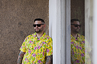 Man with fullbeard and tattoos wearing shirt with floral design and sunglasses - HCF000079