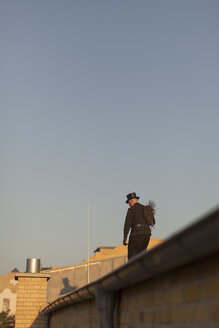 Germany, chimney sweep on rooftop - HCF000083