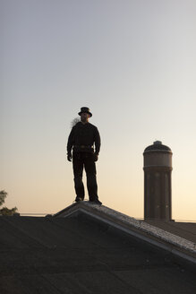 Germany, chimney sweep standing on rooftop at twilight - HCF000094