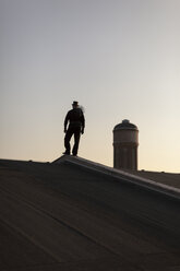 Germany, silhouette of chimney sweep standing on rooftop at twilight - HCF000086
