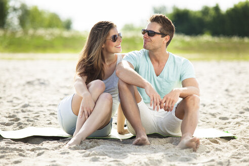 Happy couple sitting on the beach - CvKF000218