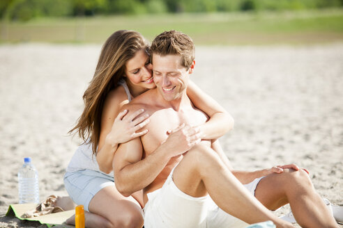 Happy couple hugging on the beach - CvKF000172
