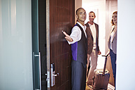 Hotel employee showing hotel guests their room - ZEF002252