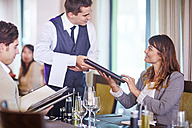 Business people placing an order with waiter  at hotel restaurant - ZEF002490