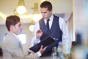 Businessman placing an order with waiter at hotel restaurant - ZEF002491
