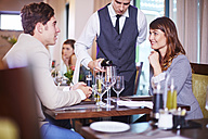Waiter pouring wine for business associates at hotel restaurant - ZEF002492