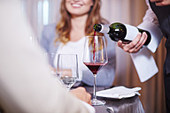 Waiter pouring wine for business associates at hotel restaurant - ZEF002261