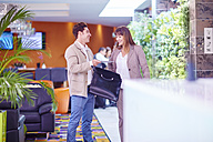 Businessman and businesswoman meeting in hotel lobby - ZEF002434