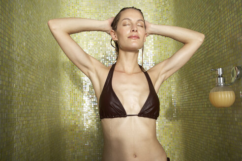 Woman taking a shower with closed eyes - FSF000397
