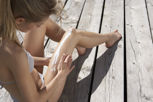 Woman sitting on planks putting on suncream - FSF000371
