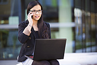 Portrait of smiling young businesswoman with laptop telephoning with smartphone - MAD000109