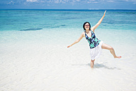 Maldives, Ari Atoll, young woman standing in the water on one leg - FLF000574