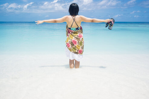 Maledives, Ari Atoll, young woman standing in water at seafront - FLF000588