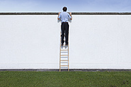 Business men with ladder on wall - RBF002217