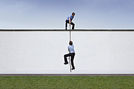 Business man helping colleague to climbing on rope over wall - RBF002226