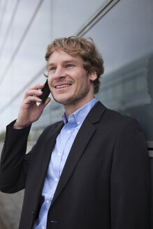 Portrait of smiling businessman telephoning with smartphone - RBF002069