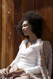 Sunbathing young woman leaning on wooden wall - FSF000387