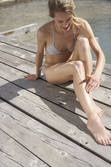 Woman sitting on planks putting on suncream - FSF000356
