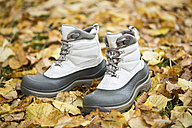 Pair of new winter boots on forest soil covered with autumn leaves - MAEF009267