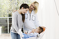 Mother and daughter looking at baby boy - GDF000582