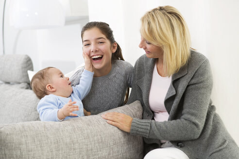 Mother sitting with daughter and baby boy on couch, smiling - GDF000591