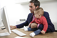 Businessman with baby boy working from home - GDF000610