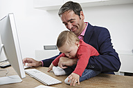 Businessman with baby boy working from home - GDF000611