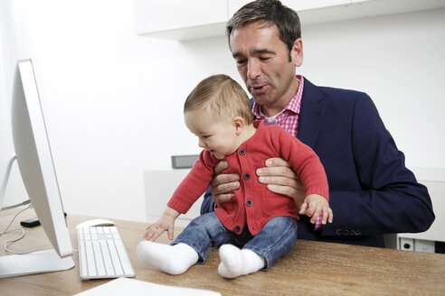 Businessman with baby boy working from home - GDF000612