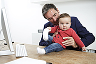 Businessman with baby boy working from home - GDF000614