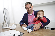 Businessman with baby boy working from home - GDF000615