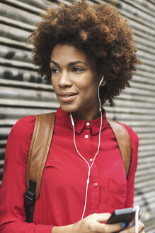 Portrait of smiling young woman hearing music with earphones - EBSF000368