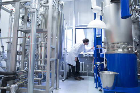 Woman with lab coat in technical room with a fermenter - SGF001077