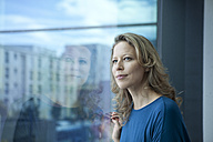 Portrait of mature woman looking through window at her apartment - RBF002039