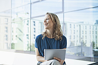 Smiling mature woman with digital tablet  sitting in her apartment - RBF002048