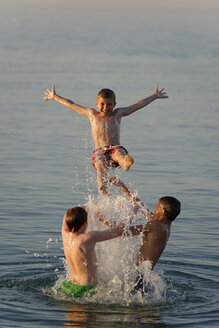 Italy, three teenage boys having fun at seaside - LBF000993