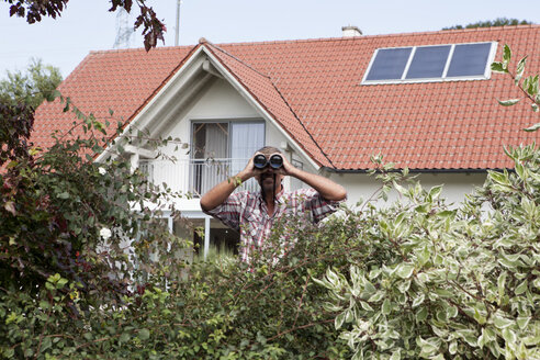 Man looking through binoculars over hedge - RBF001904