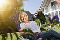 Relaxed woman in deck chair in garden - RBF001913
