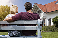 Rear view of mature couple sitting on bench in garden - RBF001940