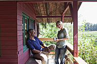 Happy mature couple on porch of summer house - RBF001949