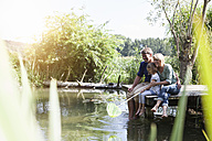 Happy family sitting with dip net on jetty at a lake - RBF001961