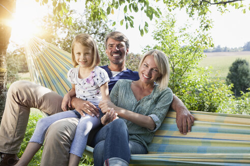 Happy family sitting in hammock - RBF001965
