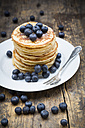 Dish with pile of pancakes, blueberries, sprinkled with icing sugar - LVF002309