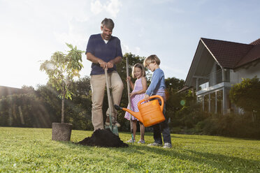 Father and children planting tree in garden - RBF002017